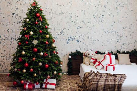 The interior of the bedroom with a green Christmas tree bed with red gifts for the new year decor winter holiday