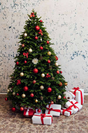 The interior of the white room is a green Christmas tree with red gifts for the new year holiday decor