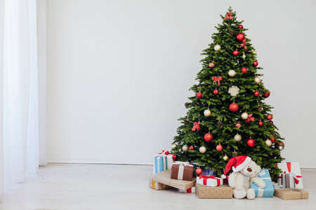 The interior of the room is a green Christmas tree with red gifts for the new year decor of the winter holiday home