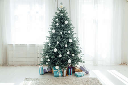 The interior of the white room with a blue Christmas tree with gifts for the new year decor winter postcard 版權商用圖片