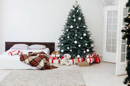 Christmas tree in the interior of the bedroom with a bed and pads for the new year