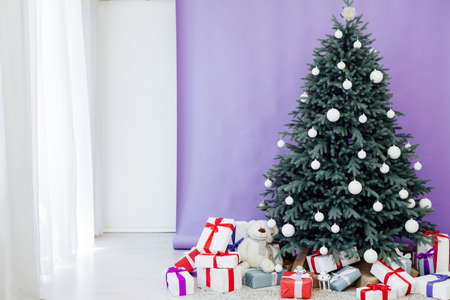 Interior with blue Christmas tree with red gifts for new year decor winter postcard purple background Stockfoto