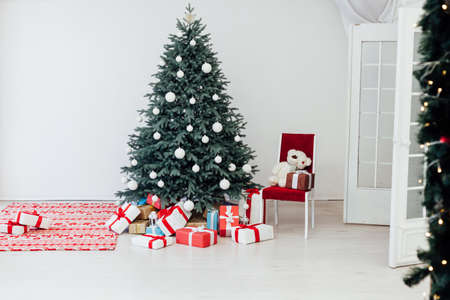 The interior of the white room with a blue Christmas tree with red gifts for the new year decor winter postcard