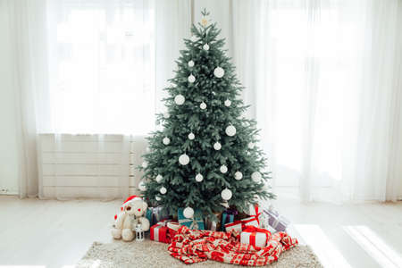 The interior of the white room with a blue Christmas tree with gifts for the new year decor winter postcard Stockfoto