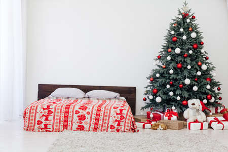 The interior of the white bedroom with a bed with a blue Christmas tree with red gifts for the new year decor winter postcard