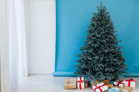 Christmas tree with gift decor for the new year winter in the white postcard room holiday blue background