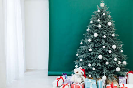 Interior with blue Christmas tree with gifts for new year decor winter green background