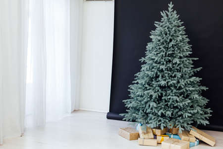 Christmas tree with gift decor for the new year winter in a white postcard room holiday black background Stockfoto