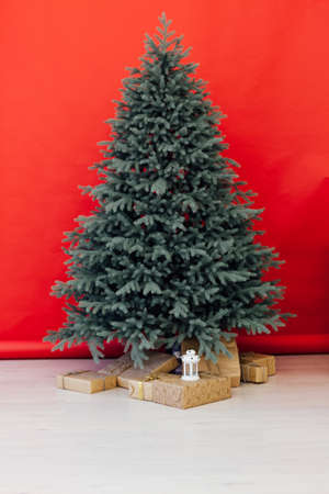Christmas tree with gift decor for the new year winter in the white postcard room holiday red background
