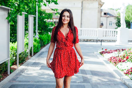Beautiful fashionable brunette woman in summer red dress on the street of the city