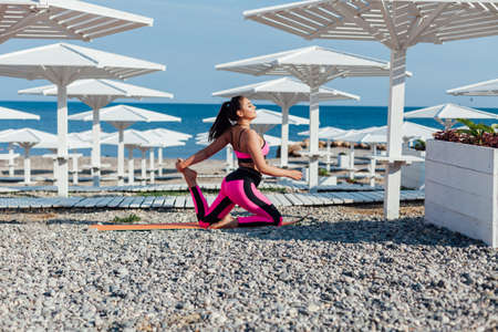 Beautiful sportswoman engaged in fitness yoga gymnastics on the beach by the sea