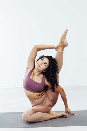 Beautiful woman yoga gymnastics flexible stretching asana fitness