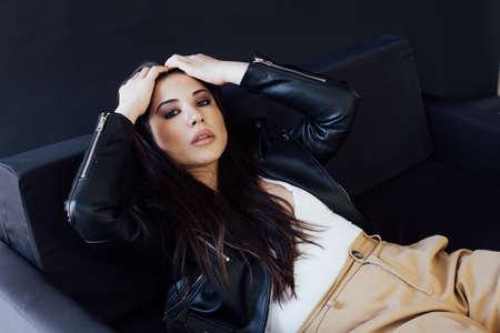 Portrait of a beautiful fashionable oriental brunette woman on a black sofa Banque d'images