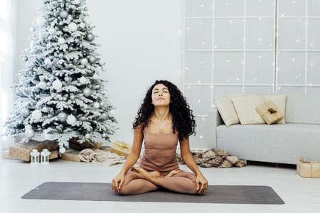 Beautiful young woman practices yoga asana Virabhadrasana at the yoga class.