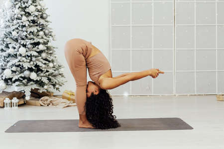 Beautiful flexible young woman is doing stretching exercise near decorated fashion christmas tree
