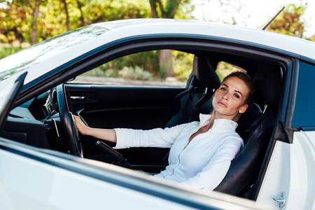 Beautiful female blonde driver behind the wheel of a car on the road