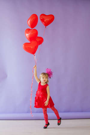 Beautiful little girl holding red balloons for the holiday