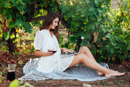 beautiful woman in white dress with laptop online and glass of wine 免版税图像