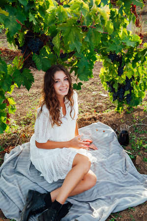 beautiful woman in dress with a glass of wine at a picnic in the vineyard