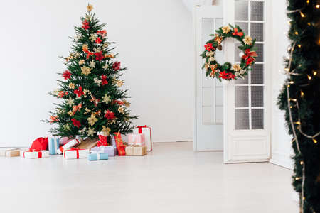 Christmas tree with decorations and gifts interior of the house new holiday white