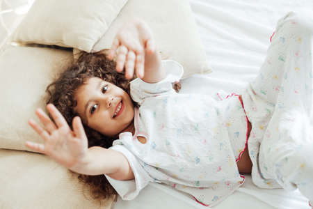 Beautiful little girl in pajamas cheerfully lies on the bed in the bedroom Standard-Bild