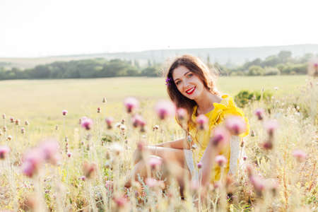 Portrait of a beautiful fashionable woman in a yellow dress in a field at sunset
