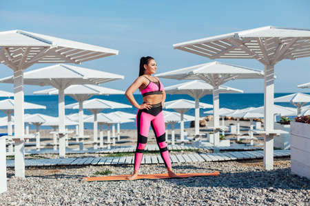Beautiful brunette woman sports gymnastics fitness yoga on the beach by the sea