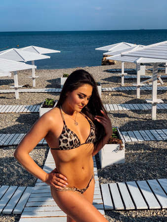 Beautiful woman in swimsuit sunbathes on the beach by the sea
