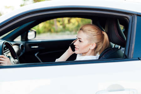 Beautiful female blonde driver talking smartphone behind the wheel of car Stock Photo