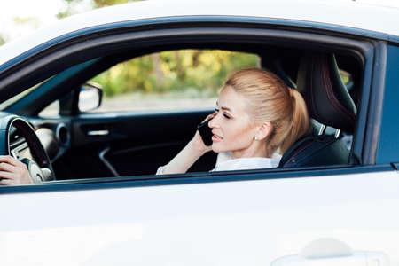 Beautiful female blonde driver talking smartphone behind the wheel of car Banco de Imagens