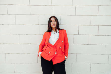 Beautiful business brunette woman in orange business suit on the street