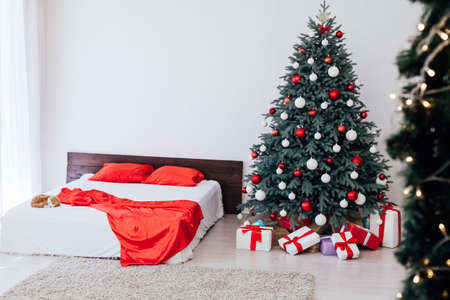A spacious white light bedroom in a loft style with a decorated Christmas tree