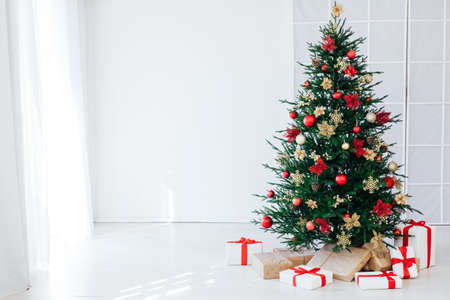 christmas tree with colorful balls and gift boxes over white wall
