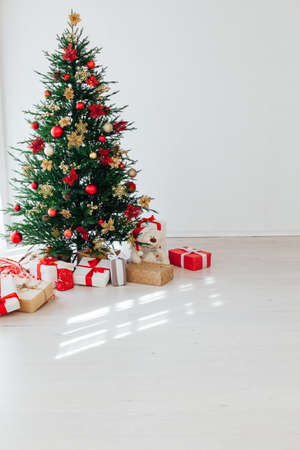 Big beautiful christmas tree decorated with beautiful shiny baubles and many different presents on wooden floor.