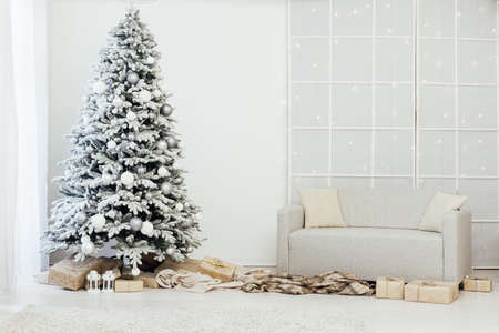Home interior. A room with a beautiful snowy Christmas tree and gifts under this tree. Stok Fotoğraf