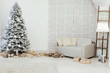 Home interior. A room with a beautiful snowy Christmas tree and gifts under this tree. Stock fotó