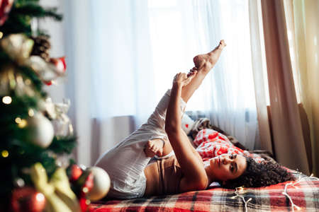 Beautiful woman yoga on the bed by christmas tree New Year Stock Photo