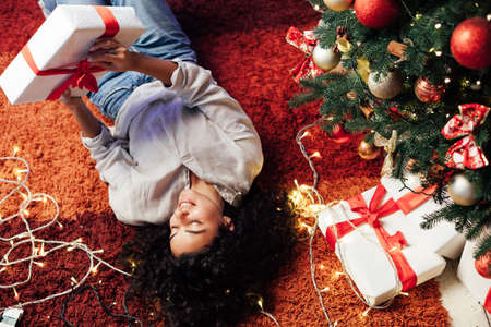Beautiful brunette woman lies near Christmas tree opens gifts for new year