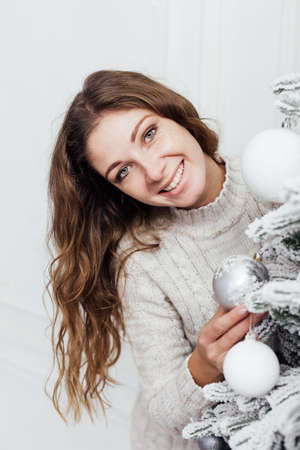 Beautiful woman decorates white snow-covered Christmas tree decor New Year