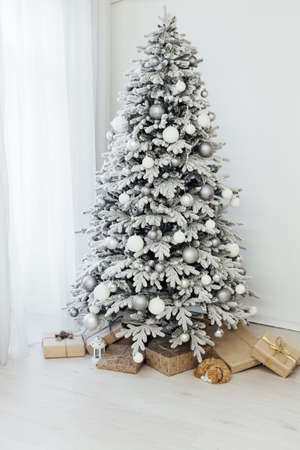 snow Christmas tree with new year gifts in the white room