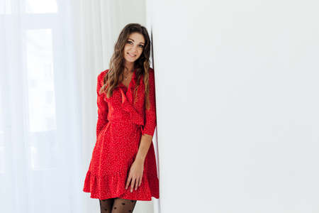 Beautiful fashionable woman in a red dress and black tights Standard-Bild