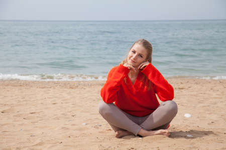 Beautiful woman blonde alone on a sandy beach by the sea 스톡 콘텐츠