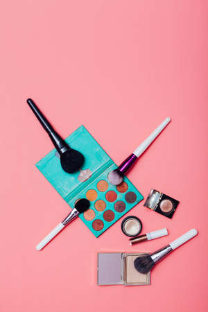 Make-up artists brushes and cosmetics styled for make-up on a pink background