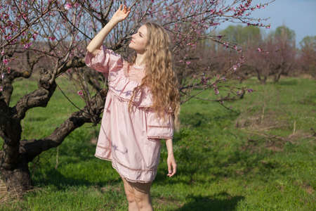 Beautiful blonde woman in pink dress in blossoming spring green garden
