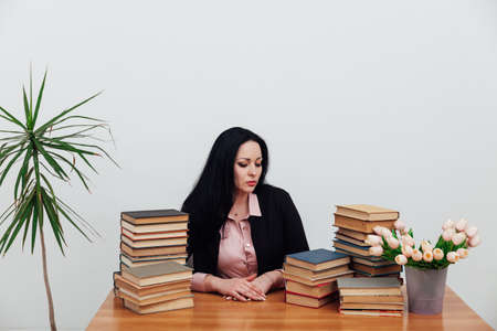 Beautiful business woman in business suit at a table with stacks of educational books