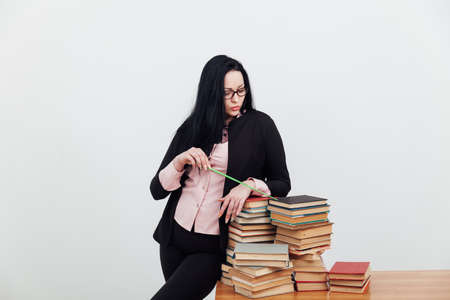 Beautiful female teacher in class at a table with stacks of educational books