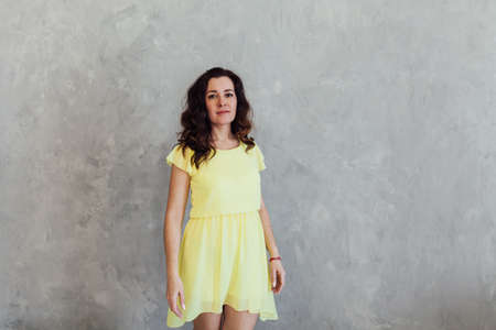 Portrait of a beautiful brunette woman in a yellow summer dress Banque d'images