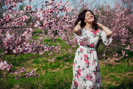 Beautiful brunette woman in a dress with flowers walks through the flowering garden in spring