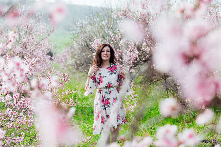 Beautiful woman in a dress with flowers walks through the flowering garden in spring