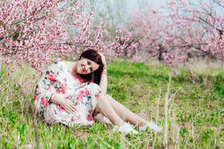 Beautiful brunette woman in a dress with flowers in pink blossoming peach garden spring